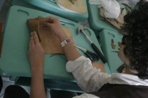 Pessoal muito concentrado montando bolsas durante oficina de couro